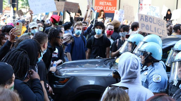 Protesters and police officers wearing riot gear have a standoff near Daley Plaza on Saturday, May 30, 2020. (Evan Garcia / WTTW News)