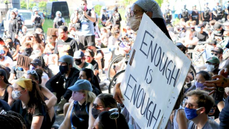 """A woman holds a sign reading """"Enough Is Enough"""" during a protest on June 2, 2020 in Old Town. (Evan Garcia / WTTW News)"""