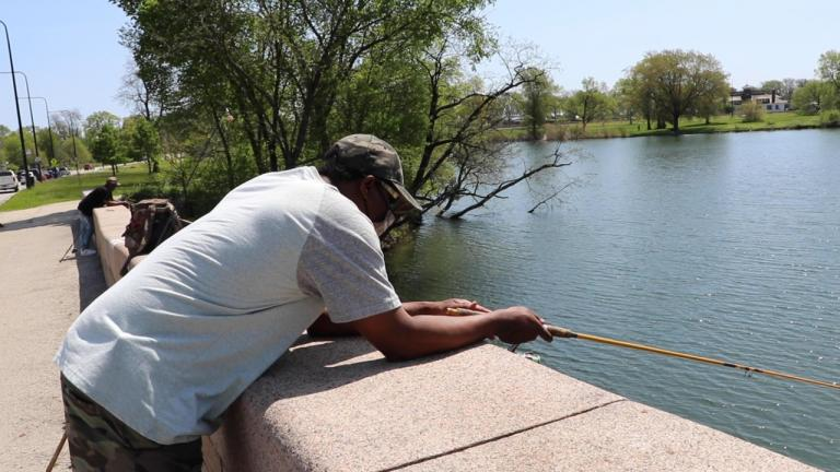 Fishermen Wayne Hankins (right) and Stephen Williams (left) fish off a bridge in Jackson Park on Chicago's South Side on May 23. (Evan Garcia / WTTW News)