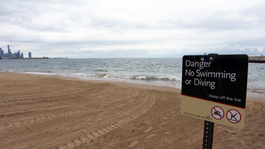 A Chicago beach sign warns people against swimming or diving in Lake Michigan. (WTTW News)