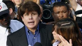 In this March 14, 2012, file photo, former Illinois Gov. Rod Blagojevich speaks to the media outside his home in Chicago as his wife, Patti, wipes away tears a day before reporting to prison after his conviction on corruption charges. (AP Photo / M. Spencer Green, File)