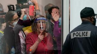 Election challengers yell as they look through the windows of the central counting board as police were helping to keep additional challengers from entering due to overcrowding, Wednesday, Nov. 4, 2020, in Detroit. (AP Photo / Carlos Osorio)