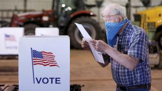 Robert Wilson reviews his selections on his ballot while voting at the town's highway garage building Tuesday, April 7, 2020 in Dunn, Wis. (John Hart / Wisconsin State Journal via AP)