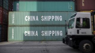 In this July 5, 2018, file photo, a jockey truck passes a stack of 40-foot China Shipping containers at the Port of Savannah in Savannah, Georgia. For months, the U.S. economy has shrugged off the tariffs slapped by America and China on tens of billions of dollars of each other's goods. (AP Photo / Stephen B. Morton, File)