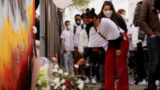 A person lays a flower at a memorial for 13-year-old Adam Toledo in Chicago's Little Village neighborhood during a peace walk on April 18, 2021. (Evan Garcia / WTTW News)