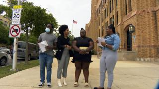 Al Raby High School teacher Jasmine Jones, second from left, and her students talk about their solar panel project. (WTTW News)