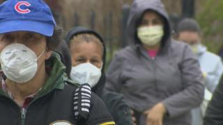 People wearing masks line up for a food drive in Brighton Park on Chicago's Southwest Side on April 23, 2020. (WTTW News)