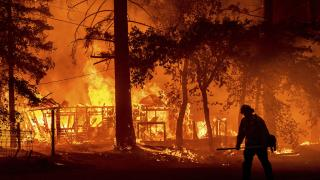 In this Saturday, July 24, 2021, file photo a firefighter passes a burning home as the Dixie Fire flares in Plumas County, Calif. (AP Photo / Noah Berge, File)
