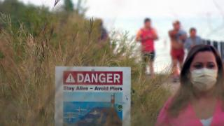 A sign on the Chicago lakefront warns people to avoid potentially dangerous areas, such as piers. (WTTW News)