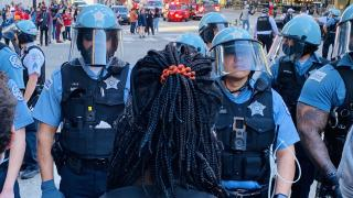 A protester faces off against police in Chicago on Saturday, May 30, 2020. (Hugo Balta / WTTW News)