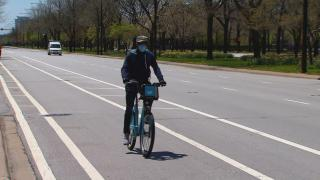 A cyclist wearing a face mask rides a Divvy bike in Chicago. (WTTW News)