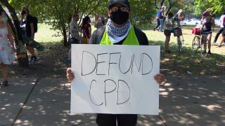 A youth activist holds a sign as part of a peaceful march to Mayor Lori Lightfoot's home on Aug. 13, 2020 to demand the removal of resource officers from Chicago Public Schools. (WTTW News)
