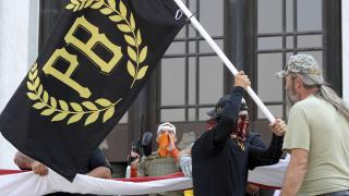 In this Sept. 7, 2020 photo, a protester carries a Proud Boys banner, symbol of a right-wing group, while other members start to unfurl a large U.S. flag in front of the Oregon State Capitol in Salem, Ore. (AP Photo / Andrew Selsky, File)