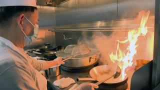 An employee of Dai Yee's Asian Kitchen cooks noodles in a wok on Mar. 2, 2021 at CloudKitchens. Dai Yee's is one of 10 restaurants renting a kitchen from the ghost kitchen located in Chicago's North Center neighborhood. (WTTW News)