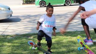 Attendees of the Go Grind youth skate camp practice tricks on the grass of Piotrowski Skate Park in Chicago. (Evan Garcia / WTTW News)
