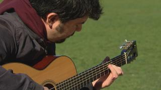 Goran Ivanovic plays guitar at a Chicago park. (WTTW News)