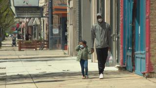 In this file photo, family members wearing masks walk along the sidewalk in the Humboldt Park neighborhood on Thursday, May 7, 2020.  (WTTW News)