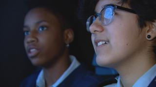 Students Tori Neealy, left, and Leah Nunez in a flight simulator at Air Force Academy High School.