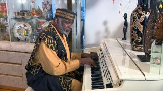 Pastor T.L. Barrett plays piano at his home on July 30, 2021. (WTTW News)