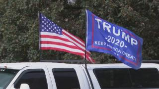 An American flag and Trump campaign flag fly at a Proud Boys rally. (WTTW News via CNN)