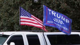 An American flag and Trump campaign flag fly at a Proud Boys rally ahead of the 2020 presidential election. (WTTW News via CNN)