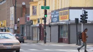 A lone pedestrian crosses the street in Chicago's Roseland neighborhood in May. Across the city, businesses and schools are closed and residents are staying home to avoid COVID-19. (WTTW News)