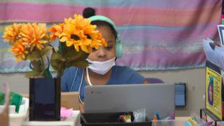 A young student wears a mask while working on a laptop. (WTTW News)