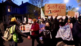 """At a protest in Logan Square on April 16, 2021, Ana Solano holds a sign reading """"Justice 4 Adam!"""" with a photograph of Adam Toledo, a 13-year-old boy fatally shot by a Chicago police officer in the Little Village neighborhood March 29, 2021. (Evan Garcia / WTTW News)"""