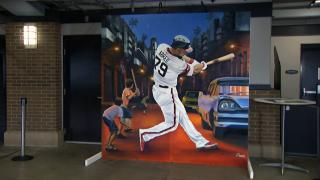 In a mural by Chicago artist Asend, a larger-than-life Jose Abreu swings his mighty bat under the Cienfuegos streetlights of his childhood. (WTTW News)