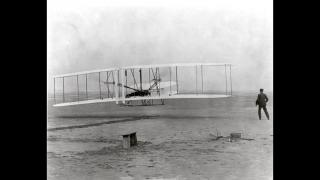 Orville Wright pilots a historic, 12-second flight on Dec. 17, 1903 at Kitty Hawk, North Carolina, as Wilbur Wright observes.