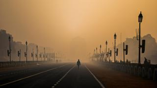 A man walks along Rajpath amid smoggy conditions in New Delhi on Jan. 28. Air pollution is shaving nearly six years off people's lives in the country, on average. (Jewel Samad / AFP / Getty Images)