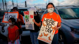 People hold signs during a DACA rally in California on June 18, 2020. (Sandy Huffaker / AFP / AFP via Getty Images)
