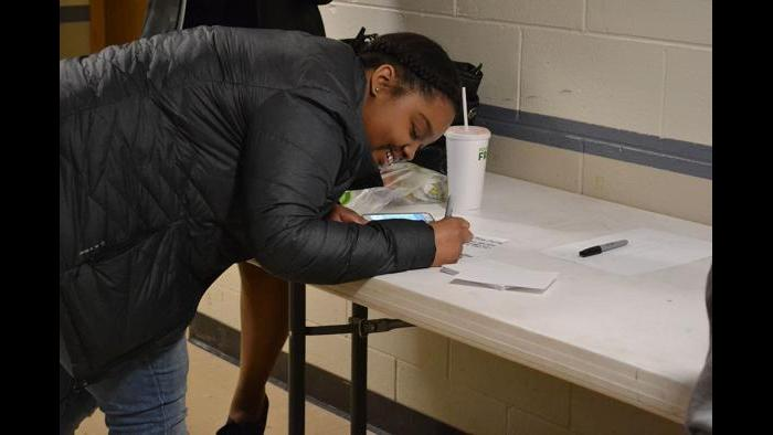 Brianna Johnson, an 11th grader at Lincoln Park High School, writes down her questions ahead of the forum.