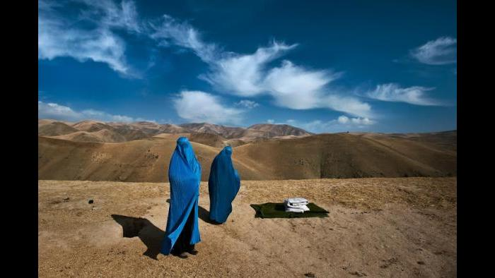 Two women from Weha Village in Afghanistan wait on the side of the road for transportation to the hospital after their vehicle had broken down during the four-hour commute. One of the women is pregnant with her first child and her water has just broke. (Lynsey Addario)