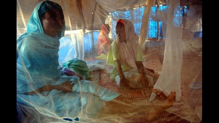 An Internally displaced mother and daughter sit beneath a mosquito net while being treated for malnutriti​on in Nyala, South Darfur, Sudan, November 2005. (Lynsey Addario)