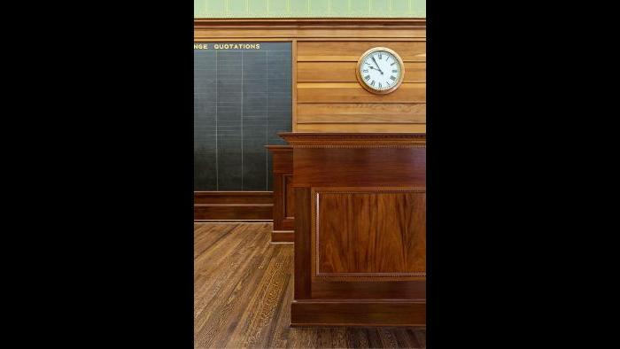 The installation of the mahogany main desk in 1980 completed the Trading Room restoration project.