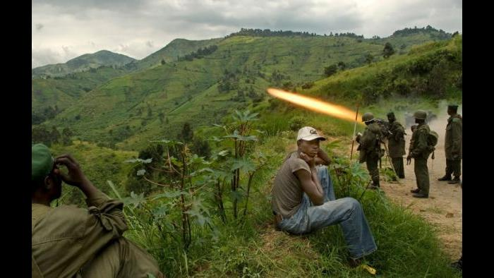 Villagers look on as the Congolese Army fires artillery at rebel soldiers under Congolese Tutsi rebel leader, Nkunda, from the village of Lushangi in the east of the Democratic Republic of Congo, December 5, 2007. (Lynsey Addario / New York Times)