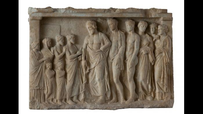 Votive Relief--In the center of this relief, Asklepios, god of medicine, leans on his staff, around which a snake is coiled. This symbol still represents medicine today. (National Archaeological Museum, Athens)