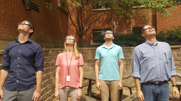 WTTW Chicago Tonight staffers line up for eclipse viewing. (Ava Martin / Chicago Tonight)
