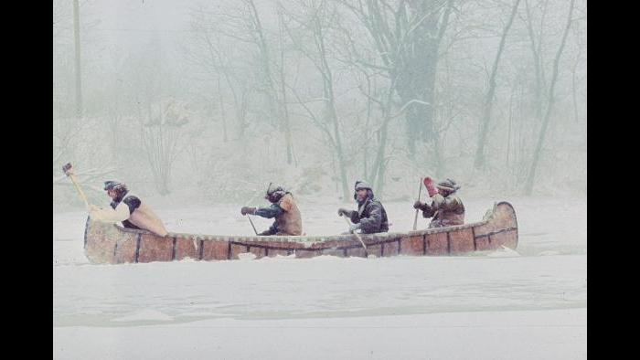 Trying to paddle down the half-frozen Kankakee River on January 5, 1977. At the front of the boat Doug Sohn uses an axe to chop through the ice while three men paddle through heavy snow behind him. (Photographers of the La Salle: Expedition II)
