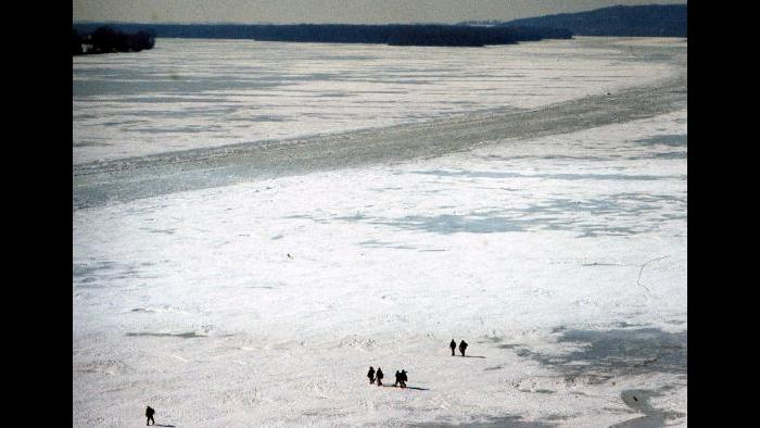 Men walk down the frozen Illinois River near Grafton, Illinois, on February 7, 1977. (Photographers of the La Salle: Expedition II)