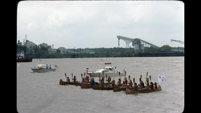 All six canoes stop for a paddle salute outside New Orleans on April 3, 1977, while a crowd and a fleet of powerboats look on. (Photographers of the La Salle: Expedition II)