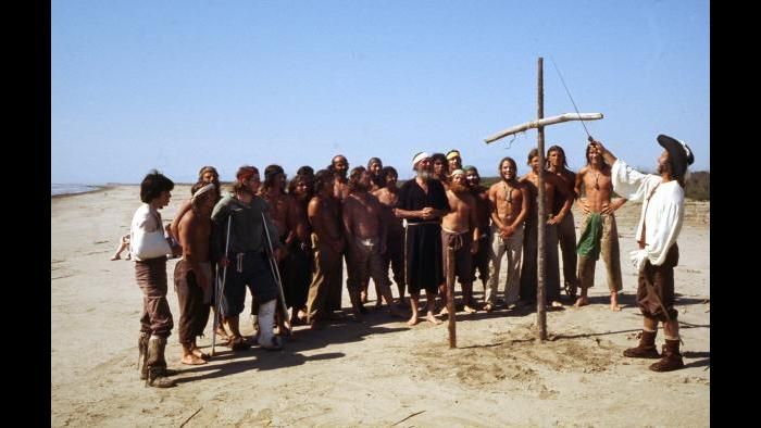 At the Gulf of Mexico at the end of their voyage, Reid Lewis claims the territory for France next to a cross made of driftwood while the crew looks on April 9, 1977. (Photographers of the La Salle: Expedition II)