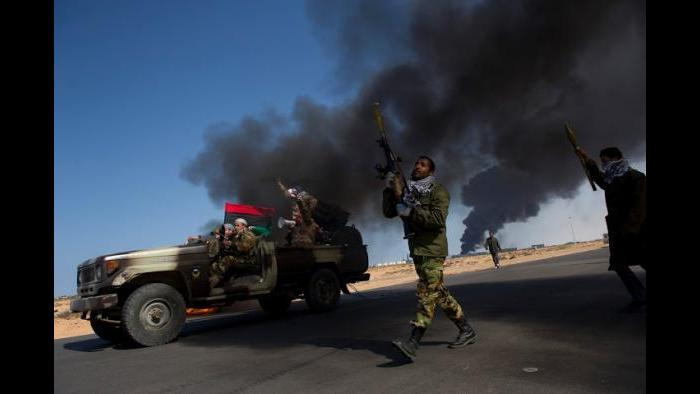 Opposition troops burn tires to use as cover during heavy fighting, shelling, and airstrikes in Eastern Libya, March 11, 2011. (Lynsey Addario / New York Times)