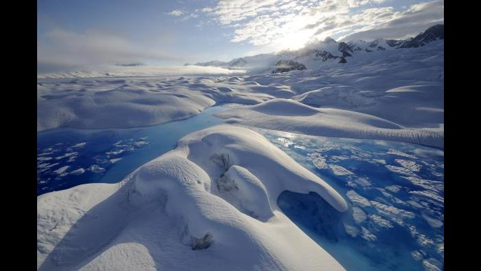 As warmer temperatures heat Alaska's Columbia Glacier, brilliant blue ponds of meltwater form on the glacier's surface. (James Balog / Museum of Science and Industry)