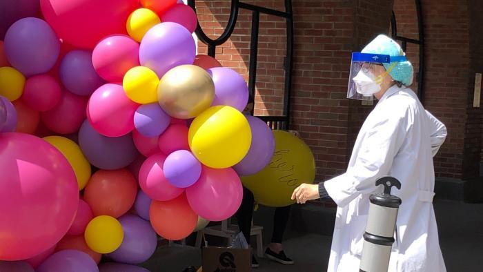 A front-line worker at Illinois Masonic checks out the balloon installation. (Patty Wetli / WTTW News)