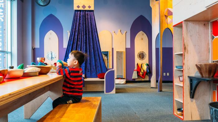 """A young child plays at the communal table at the """"Once Upon a Castle"""" exhibit. (Courtesy of Chicago Children's Museum)"""