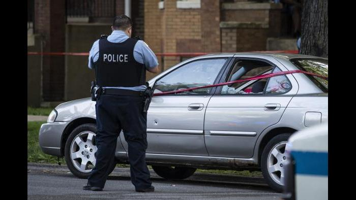 A Chicago police officer investigates the scene of a shooting in Chicago on Sunday, July 5, 2020. (Ashlee Rezin Garcia / Chicago Sun-Times via AP)
