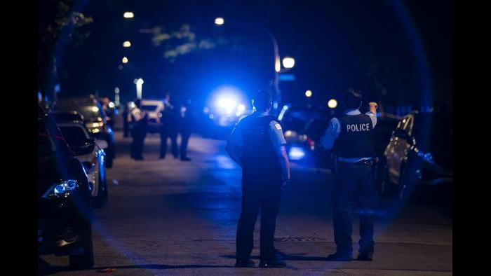 Chicago police officers investigate the scene of a shooting in Chicago on Sunday, July 5, 2020. (Ashlee Rezin Garcia / Chicago Sun-Times via AP)