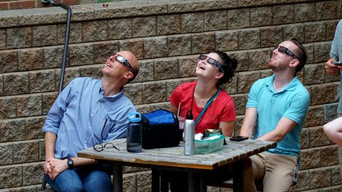 WTTW Chicago Tonight staffers take a break to look at the sky. (Alexandra Silets / WTTW)